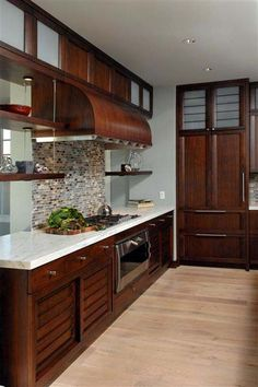 Dark cherry cabinets, light countertops, pretty backsplash.