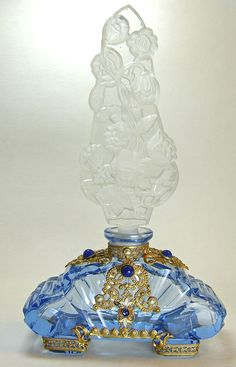 Large Blue Base Czech Jeweled Perfume Bottle.  This 1925-38 Czech jeweled perfume has a double intaglio stopper. Both sides are moulded with frosted roses that rise on vines from a lattice base. Both sides are also surface polished and the edges are frosted. The face & shoulders are decorated with gold plated filigree set with Lapis glass stones, white enamel and faux pearls. The square feet are also wrapped with the filigree.