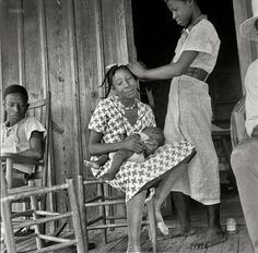 Black Woman doing hair. Near Earle, Arkansas. (July 1936.)