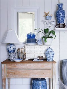 Blue china dishes on white wash walls with aged wood furniture paves the way for that antique charm.