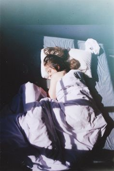 She rolls to the window as she is woken by the light on her face. Rolling back on her back, she raises her torso holding herself up with her hands.