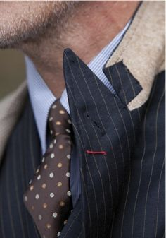 See that red thread?  When you stick your flower through the lapel button hole, secure it with that thread.  Classic.  The sign of a high quality suit.