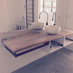 Modern recycled timber vanity bench top with matte black tap ware and towel rail…