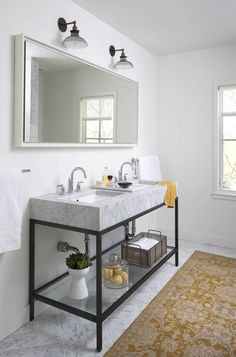 White walls, a luxurious marble double-sink, and an area rug give this bathroom an inviting atmosphere.