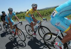 Vincenzo Nibali (C) of Italy and the Astana Pro Team in the overall leader's yellow jersey rides in the protection of teammtes Jakob Fuglsang (L) of Denmark and the Astana Pro Team and Dmitriy Gruzdev (R) of Kazakhstan and the Astana Pro Team during the twelfth stage of the 2014 Tour de France, a 186km stage between Bourg-en-Bresse and Saint-Etienne, on July 17, 2014 in Saint-Etienne, France.