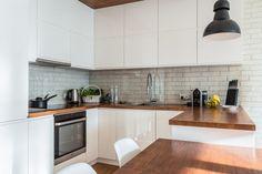 Białe szafki o gładkich frontach z połyskiem wprowadzają nieco nowoczesnego charakteru do skandynawskiej kuchni. Czarne...