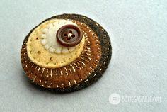 spilla tonda, con cerchi disposti asimmetricamente sui toni del marrone e decorato con filo dorato.