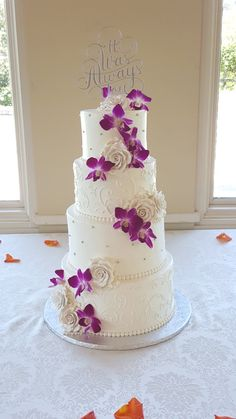 A beautiful four-tiered wedding cake with sugar flowers and purple and white dendrobium orchids from Seasonal Celebrations.