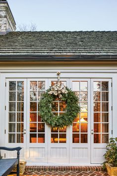Wreath on a Colonial-Style Home A large green wreath with gold ribbon decorates the doors from the terrace to the garden room. Styling by Jane Schwab with Jay Lugibihl. Photography by Laurey W. Estilo Colonial, Colonial Style Homes, Decoration Christmas, Noel Christmas, Holiday Decorations, Holiday Wreaths, Christmas Stuff, The Doors, Family Room Fireplace