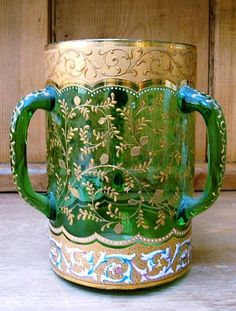 """Moser 3-Handled Green Enameled Tyg or Loving Cup. A (Ludwig) Moser Three Handled Loving Cup, Circa 1870-1895. It is Green Glass with a Blue, Pink Yellow and White Enamel and Gilt Floral Design All Over, including the handle. From Karlsbad in Bohemia, now the Czech Republic. Dimensions; 7"""" high x 4.75"""" width at the top and 6"""" to handles. Excellent condition."""