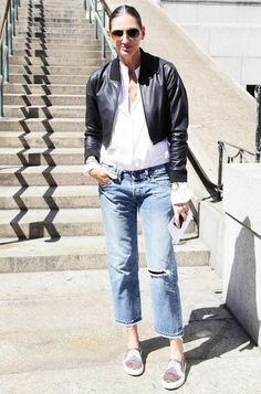 Jenna Lyons in a black leather bomber jacket _ white button-up _ distressed boyfriend jeans + slip-on sneakers
