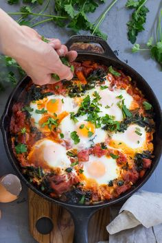 Eggs simmer in a spicy tomato sauce with kale and sausage in this savory and filling Shakshuka. Paleo and Whole30 and great for any meal!