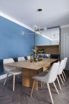 No clima azul das paredes, o sofá e o tapete escolhidos são da mesma cor. No centro, um pufe ao lado da mesinha serve como apoio ou assento. E na parede, a bicicleta de treino externo.