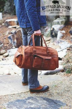 The Kipling Leather Duffle Bag is made from genuine leather with antique brass rivets and hardware. The full grain leather is finished and tanned in a camel color.  mens fashion | duffel bag leather | mens casual style