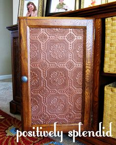 Faux tin panels to replace glass cabinet doors...may have to try this.
