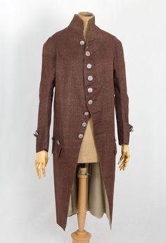 1780s man's wool coat made from sturdy brown wool tweed and lined with cream colored silk twill. The silver-tone metallic buttons are later replacements. The coat has deep front pockets with flaps, a stand-up collar, wide cuffs, and pleated back vents.