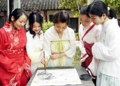 Women dressed in ancient Chinese costumes practice ink painting in Suzhou, Jiangsu province on April 15, 2006.