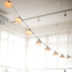 Pleated String Lights MADE TO ORDER by PigeonToeCeramics on Etsy / A set of ten unglazed porcelain shades with a tiered surface cast ultra thin for translucency strung up on an indoor/outdoor 11 green cord with 12 bulb spacing.