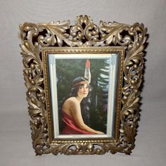 """This listing is for an ornate metal table top frame. It houses a small vintage calendar print of a Native American Indian Maiden. The calendar print is titled """"Weejanwah - Little Wom..."""
