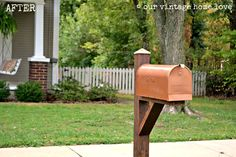 mailbox sprayed with metallic spray paint and stained post