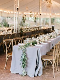 Garland draped tables + tented reception perfection: http://www.stylemepretty.com/2016/02/11/classic-springtime-dunaway-gardens-wedding/   Photography: Amy Arrington - http://www.amyarrington.com/