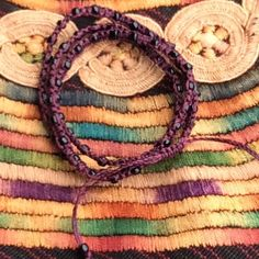 """Aubergine """"Xubal Handmade Bracelet from Guatemala"""" In Aubergine with black beads, 26"""" around, 100% Poly Waxed Thread, Metal Beads, Handmade by skilled artisans in Guatemala, mix & match! For sale as individuals or with Ketzali """"Tzuel Textile Pouch""""- $32., with Makeup bag- $42, with Makeup bag, Pouch, and 1 Bracelet- $58, with 2 Bracelets- $72. Ketzali Jewelry Bracelets"""