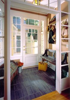 This mudroom addition creates a perfect dropping ground before you enter the new family room. A slate floor is forgiving of muddy and wet feet and makes for easy clean up. Lots of light with transoms into the interior family room and exterior adds function to beautiful form. Photography: John Umberger; Real Images 2002 Chrysalis Award - Addition Over $250K Junior League Tour of Kitchens 2002 Featured in Sept 2003 Better Homes Gardens Magazine  Sunny Dispositions Featured in Oct 2006 Atlanta…