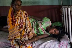 A young woman is comforted by her mother-in-law while in labor in the maternity ward at the Dhekiajuli Community Health Center in Assam, India. April 8, 2015.