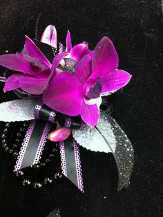 Wrist corsage of purple dendrobium orchids, silver leaves, and black and purple ribbon on a black and silver band.                                   Created by Hawley's Florist