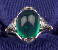 Art Deco Platinum, Emerald and Diamond Ring, set with a cabochon emerald measuring approx. 11.10 x 9.02 x 8.42 mm, gallery and shoulders bead-set with twenty full and old single-cut diamonds, millegrain accents