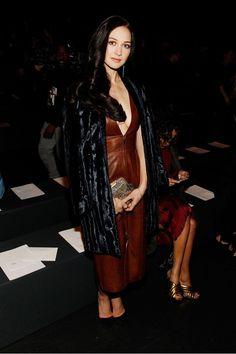 Hannah James wears a leather midi dress, fur coat, and pumps