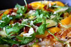 Pizza mit getrockneten Tomaten, Thunfisch, Rucola und frisch gehobeltem Parmesan