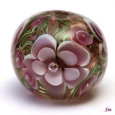 Květinová vinutka Něžná Něžná autorskákvětinová vinutka o velikosti 2,1 a 1,7 cm. Podkladz transparentní růžové, fialová kvítka. Velikost dírky 2 - 3 mm.