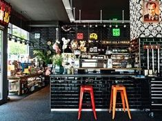 Toykio Coffee & Gallery, Düsseldorf hotels and restaurants exhibit design. Bright industrial tolix stools against black = striking design! Deco Restaurant, Restaurant Interior Design, Cafe Interior, Deco Design, Cafe Design, Küchen Design, Café Bar, Coffee Shops, Coffee Cafe