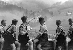 Boys of the German Youth are sitting on a wall in front of the youth hostel Johanngeorgenstadt and have a look at the landscape, in July 1937. Photo: Berliner Verlag/Archiv