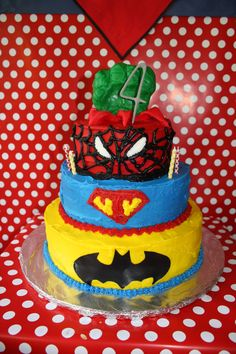 """Super Hero Birthday cake!  The Batman layer is chocolate, Super """"T"""" layer is red velvet, spiderman layer is strawberry, and the hulk hand is rice krispy treats covered in fondant."""