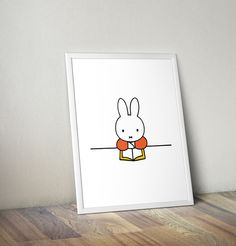 """Miffy reading a book, Framed Wall Art. Featuring Dick Bruna's unmistakable illustrations, this beautiful mini poster is a must for all Miffy fans. The combination of these minimalist designs and bright primary colours makes this piece a must-have work of art. Framed in a simple contemporary white moulding. Printed on 11x14"""" (28x36cm), Semi-Matte 280gsm Gallery Grade Paper. £18 athomeshopping.co.uk"""