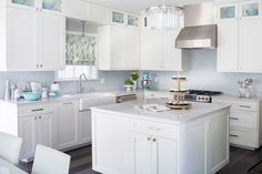 An all white kitchen with light blue tiled backsplash, and a chandelier over the center island.