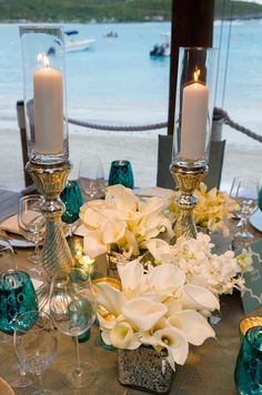 Low calla lily arrangements are paired with silver pillar candles to enhance the ornateness of the table. Aqua Wedding, Wedding Table, Wedding Flowers, Wedding Turquoise, Wedding Ideas, Reception Decorations, Wedding Centerpieces, Table Decorations, Photos Booth
