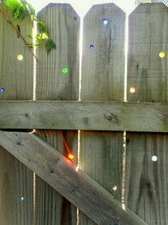 Drill a hole thru the fence, add marbles & clear silicone if you want a more secure fit.  Charming backyard look.