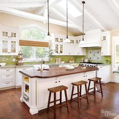 Once a cramped room tucked away from the rest of the house, the kitchen is now an integral part of surrounding living spaces. Expanding the kitchen upward and outward ushered in natural light and breathing room. The new layout includes a wood-topped island and professional-style range. A glass subway tile backsplash and granite countertops include various shades of green that pop against the classic white cabinetry.