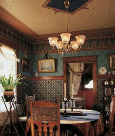 18th-19th century Victorian style living area. Dark woods were very popular in this era and the more furniture you had represented wealth. These owners took great pride in their home creating a space for entertainment. Bulky ornamentation and wallpaper is used in this room. Rich colours were also popular in this period.