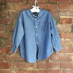 GAP boys light weight denim shirt GAP boys light weight denim shirt. Collarless with red plaid detail on the inside rim of neck. Bottom down . Size XS 3-4 toddler.be sure to bundle for great savings! GAP Tops Button Down Shirts