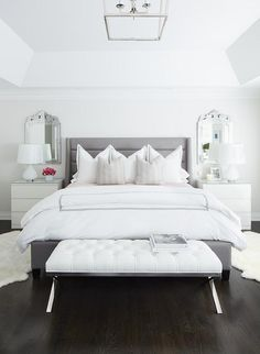 A White Leather Tufted Bench Is Placed In Front Of Gray Channel Bed Dressed