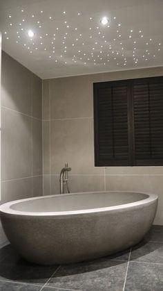 Mooi robuust Lavastone (betonlook) vrijstaand ligbad. Ro-stone serie van ADW Design. Luxe sfeervolle sterrenhemel van Luxalon in plafond. Zie ook www.welbie.nl.