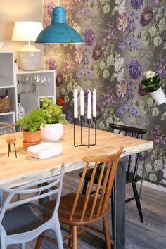 Näyttävä kukkatapetti ja eri paria olevat tuolit ruokailutilassa