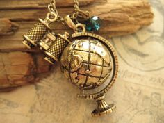 Around the World. Rotating Globe Necklace with binocular charm and crystal accent. $9.99, via Etsy.