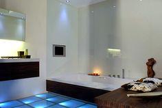 Com chão iluminado e banheira retangular.