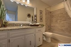 Traditional Full Bathroom with limestone tile floors, Drop-In Bathtub, High ceiling, Complex Granite, Flat panel cabinets
