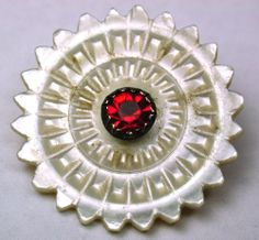 antique carved mother of pearl shell button. Lovely carving with pretty red glass jewel in brass setting in center. Circa late 1700s. Very good condition. Measures 7/8 inch.  SOLD $132.50
